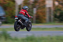 """A woman rides a motorcycle, also referred to as a """"crotch rocket"""" down a highway in Minnesota"""