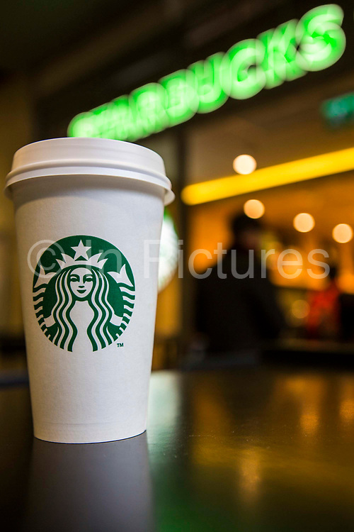 A Starbucks coffee cup sitting on a table outside Starbucks coffee shop, Canary Wharf. London, UK.