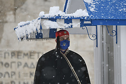 """Presidential guard """"Evzonas""""   during a rare heavy snowfall in the city on February 16, 2021."""