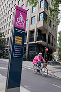 A cyclist rides past annual cycling statistics for the North-South CS6 Superhighway that allows commuters safe journeys south of Blackfriars Bridge, on 22nd June 2021, in London, England.