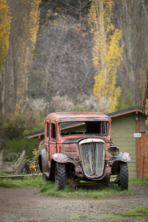 View of vintage, old car in front of wood cabin in middle of autumnal forest in Bariloche, Argentina