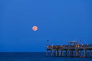 The full moon rises over the public fishing pier at Dania Beach, Florida. WATERMARKS WILL NOT APPEAR ON PRINTS OR LICENSED IMAGES.