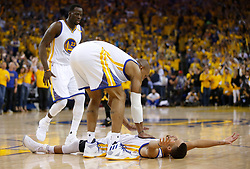 The Golden State Warriors' Stephen Curry, bottom, is congratulated by teammate David West after making a basket and getting fouled against the Cleveland Cavaliers in the second quarter of Game 5 of the NBA Finals at Oracle Arena in Oakland, Calif., on Monday, June 12, 2017. (Photo by Nhat V. Meyer/Bay Area News Group/TNS) *** Please Use Credit from Credit Field ***