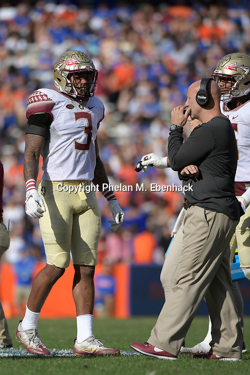 Florida State defensive back Derwin James (3) talks with defensive coordinator Charles Kelly during the second half of an NCAA college football game against Florida Saturday, Nov. 25, 2017, in Gainesville, Fla. FSU won 38-22. (Photo by Phelan M. Ebenhack)