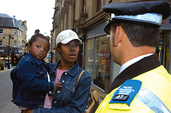 Police Community Support Officer chats to members of public in the street Bradford Yorkshire UK