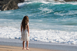 A young girl stands on Fistral beach in Newquay, Cornwall.
