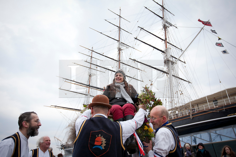 © Licensed to London News Pictures. 01/04/2013. London, UK. Cati Campos from Majorca, Spain, is lifted into the air on a chair by members of the Blackheath Morris Men as part of an Easter ritual in Greenwich, London, today (01/04/2013).  The tradition, known as 'Easter Lifting', involves the lifting of a female volunteer into the air three times before being asked to kiss each of those doing the lifting.  Photo credit: LNP