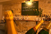 The gourmet Restaurant Le Jardin d'Ausone in the old town in Bordeaux: the bar with champagne bottles in the foreground and glasses on a shelf in the background