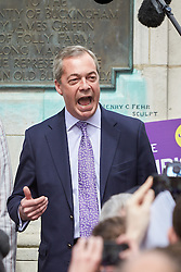 © Licensed to London News Pictures.  30/04/2015. AYLESBURY, UK. Nigel Farage (centre), UKIP party leader, gives a short speech in front of a statute of John Hampden, an parliamentarian who challenged the authority of the King ahead of the English Civil War, during a campaign visit to Aylesbury. <br /> <br /> Photo credit: Cliff Hide/LNP