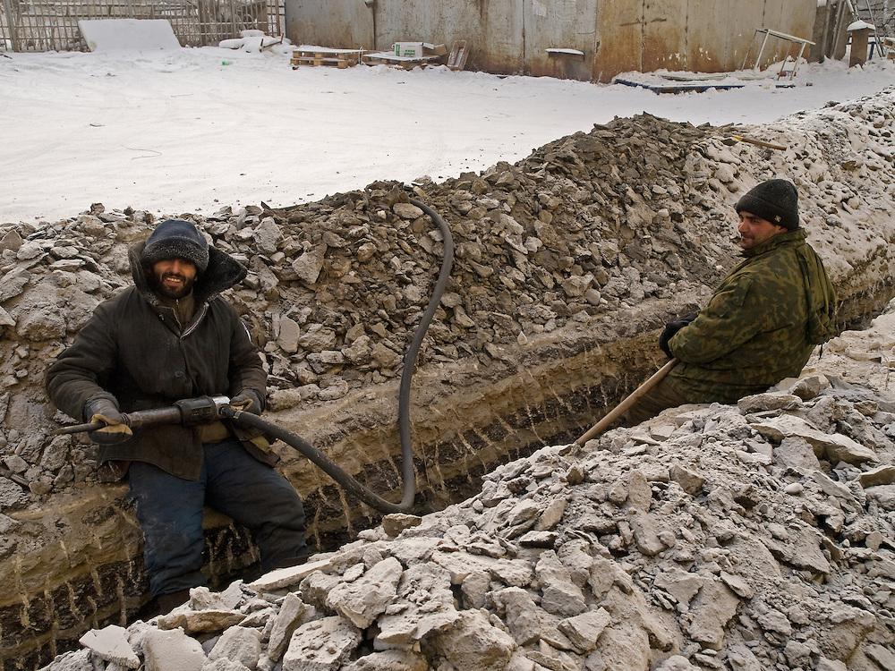 Portrait von Gastarbeitern waehrend Arbeiten mit einem Presslufthammer um den tiefgefrorenen Boden bei einer Aussentemperatur von -31 Grad Celsius zu oeffnen. Jakutsk wurde 1632 gegruendet und feierte 2007 sein 375 jaehriges Bestehen. Jakutsk ist im Winter eine der kaeltesten Grossstaedte weltweit mit durchschnittlichen Winter Temperaturen von -40.9 Grad Celsius. Die Stadt ist nicht weit entfernt von Oimjakon, dem Kaeltepol der bewohnten Gebiete der Erde.<br /> <br /> Guest workers from other parts of the Russian Federation digging in the deeply frozen ground during temperatures around -31 degrees Celsius in the city center of Yakutsk. Yakutsk is a city in the Russian Far East, located about 4 degrees (450 km) below the Arctic Circle. It is the capital of the Sakha (Yakutia) Republic (formerly the Yakut Autonomous Soviet Socialist Republic), Russia and a major port on the Lena River. Yakutsk is one of the coldest cities on earth, with winter temperatures averaging -40.9 degrees Celsius.