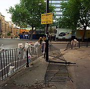"In front of car ad billboards, a memorial has been placed where 'Jay' died on St George's Circus, London, England. If we drove past this place where someone's life ended, the victim would just be a statistic but flowers are left to die too with touching poems written by family and loved-ones: ""Everything you touched turned to gold"" From a project about makeshift shrines: ""Britons have long installed memorials in the landscape: Statues and monuments to war heroes, Princesses and the socially privileged. But nowadays we lay wreaths to the ordinary who die suddenly - killed as pedestrians, as drivers or by alcohol, all celebrated on our roadsides and in cities with simple, haunting roadside remembrances"