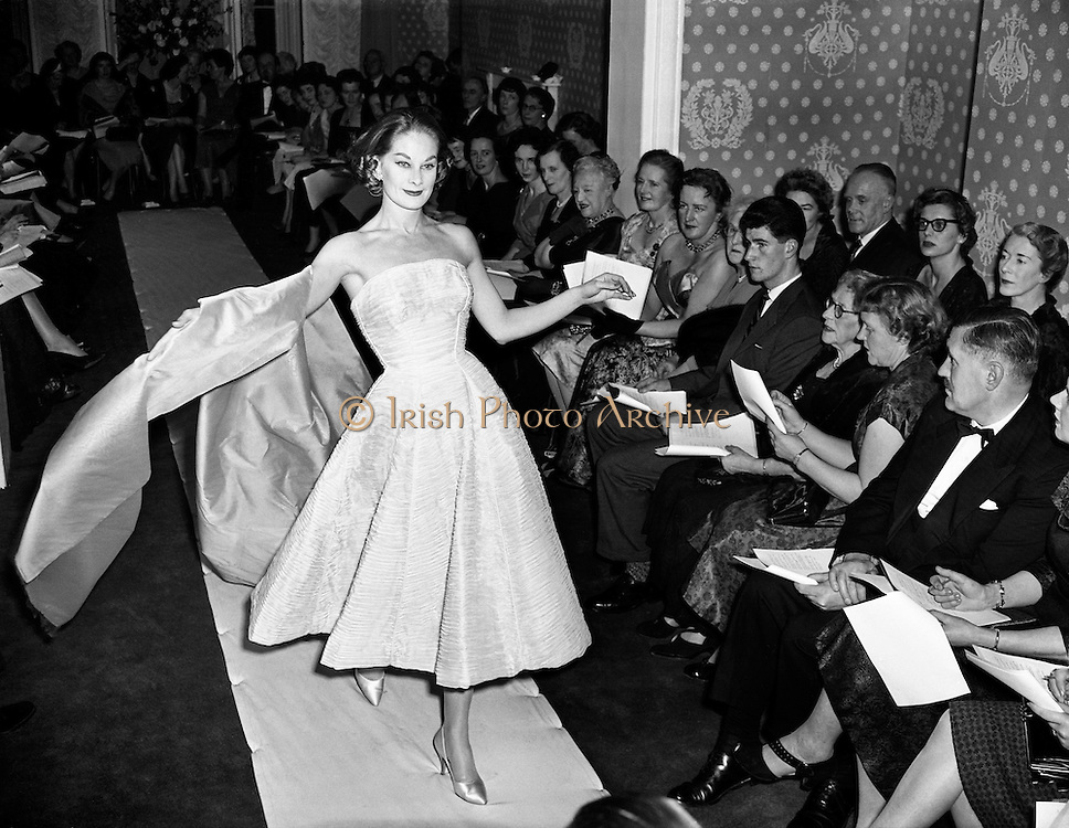 Sybil Connolly Fashion Show at New Premises at Merrion Sq..17/01/1958..Sybil Connolly (24 January 1921, Swansea, Wales - 6 May 1998, Dublin) was an Irish fashion designer for Brunschwig & Fils, F. Schumacher & Co., Tiffany & Co., etc. She was named to the International Best Dressed List Hall of Fame in 1965..Sybil Connolly was born to a Welsh mother and an Irish father; they moved to County Waterford, where she was educated at a convent school run by the Sisters of Mercy. Her interest in fashion led her to London, aged 17, to study dressmaking with Bradley & Co..Her clothes were sought after in the United States and she had an impressive list of clients from prominent families such as the Rockefellers, Mellons and Duponts, to famous actresses of the day. Jacqueline Kennedy wore a Sybil Connolly creation when she sat for her official White House portrait and visited the designer in Ireland. A showcase for her excellent taste in interior decoration, her home was featured in House Beautiful in 1967.[citation needed].In the 1980s, Sybil Connolly began designing for luxury goods makers Tiffany & Co of New York, Tipperary Crystal, Brunschwig & Fils, and Schumacher. Connolly lived at 71 Merrion Square in Dublin for many years and died there in May 1998. Considered one of Dublin's finest Georgian Squares, Merrion Square was first laid out in 1762 and mostly completed by the beginning of the 19th century. Now home to a number of prestigious organizations, including the Irish Red Cross, the National Gallery of Ireland and the National Museum of Ireland, the square was mainly residential up until the 1960s. The square boasted a number of notable residents during its history, including Oscar Wilde at No. 1, the poet William Butler Yeats at No. 82, and at No. 58, Daniel O'Connell, an Irish politician and campaigned for Catholic emancipation..She returned to Ireland at the outbreak of World War II and lived there for the rest of her life, making her home at number 71 Merrion