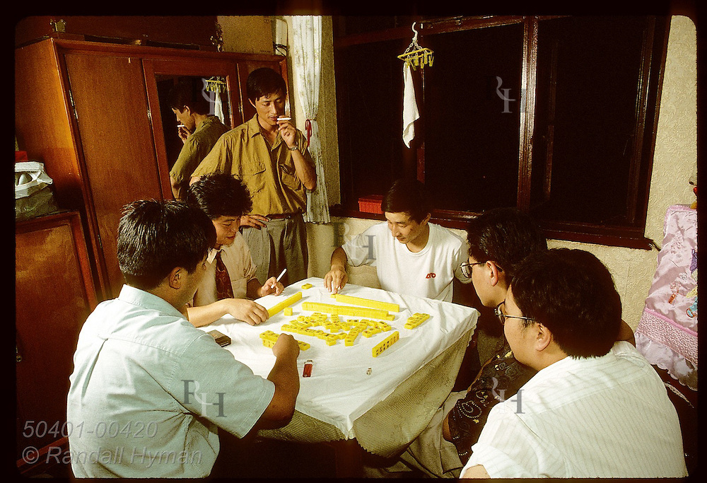 Businessmen play mah-jongg around table in tiny apartment after long day at office in Shanghai. China