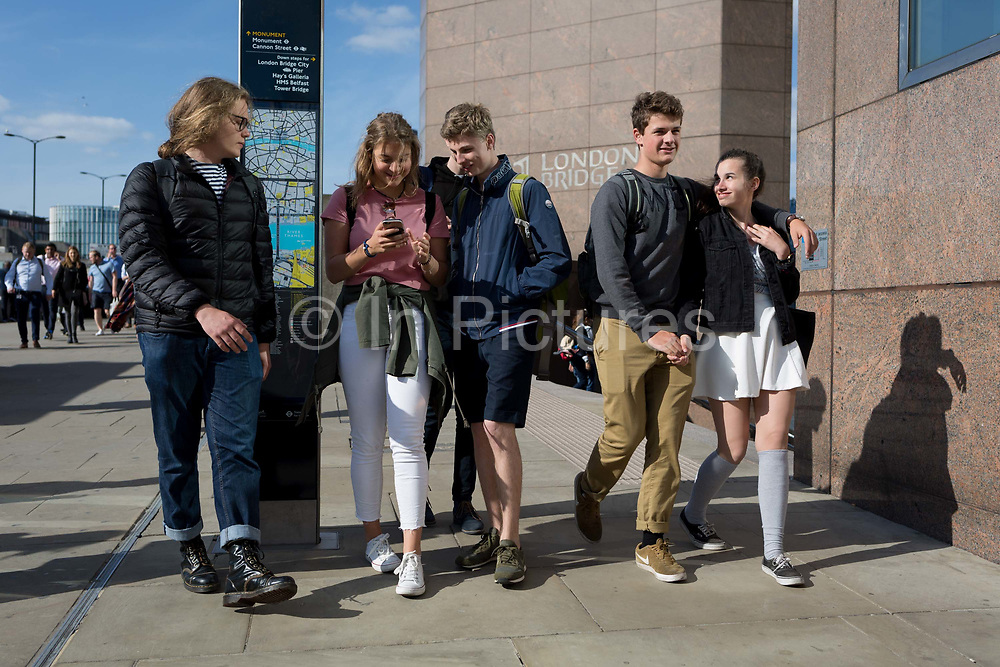 Friends, commuters and other pedestrians walk over London Bridge, the oldest of the capitals crossing over the river Thames between the capitals financial district, the City of London, and Southwark on the south bank, on 17th May 2018, in London, UK.