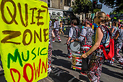 Members of the Batala drum band from Brazil stop playing to honour a quiet zone to remember the Grenfell Tower tragedy - The Monday of the Notting Hill Carnival. The annual event on the streets of the Royal Borough of Kensington and Chelsea, over the August bank holiday weekend. It is led by members of the British West Indian community, and attracts around one million people annually, making it one of the world's largest street festivals.