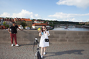 A young lady from South Korea is photographing herself with a camera triggered via her smart phone and live view on Charles Bridge in Prague. The Charles Bridge (Czech: Karlův most) is a famous historic bridge that crosses the Vltava river in Prague, Czech Republic and is probably the Nr.1 tourists magnet in the city.