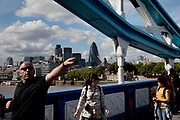 Tourists cross Tower Bridge. The newly repainted bridge is a big draw for tourism. In the distance over the River Thames is the City of London financial / banking district including the distinctive Gherkin.
