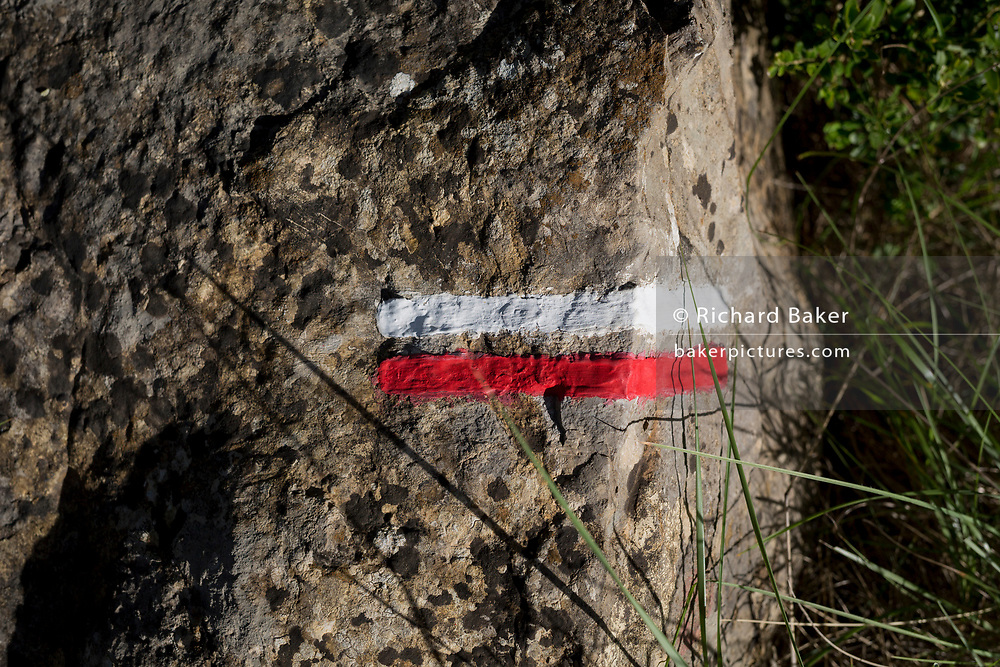 Detail of red and white stripes painted on a rock showing cross-country walkers the route on French national trekking network, the GR36, on 21st May 2017, in Lagrasse, Languedoc-Rousillon, south of France. Lagrasse is listed as one of France's most beautiful villages and lies on the famous Route 20 wine route in the Basses-Corbieres region dating to the 13th century.