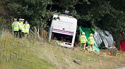 © London News Pictures. 11/09/2012. Hindhead, UK . Emergency services at the scene of a fatal bus crash on the north bound A3 motorway near Hindhead Tunnel, Hindhead, Surrey on September 11, 2012.Three people were killed and a number of others seriously injured when a coach carrying overturned after crashing into a tree. Photo credit: Ben Cawthra/LNP