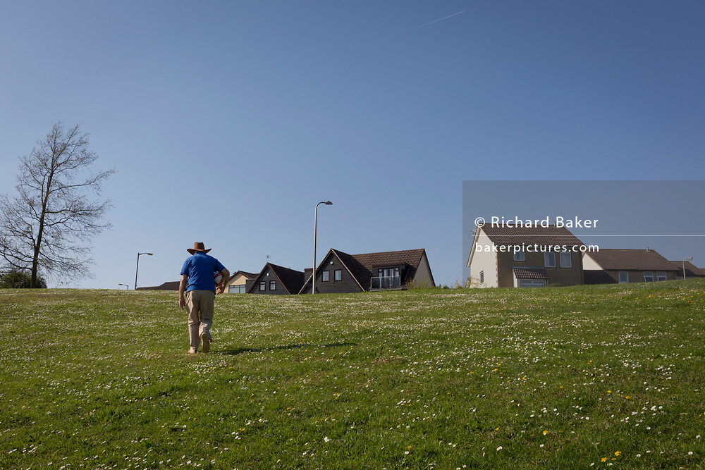 An elderly man walks uphill towards the houses of a nineteen-eighties, middle-class housing estate on 21st April 2019, in Nailsea, North Somerset, England