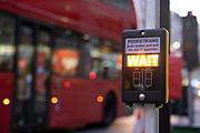 The Wait sign is illuminated while a London bus passes a crossing at the top of Ludgate Hill in the City of London, on 26th February 2021, in London, England.