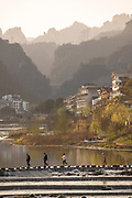 Scenic shot of river with stepping stones and view of the houses and Chinese style architecture in Zhangjiajie city in the background, Hunan Province, China