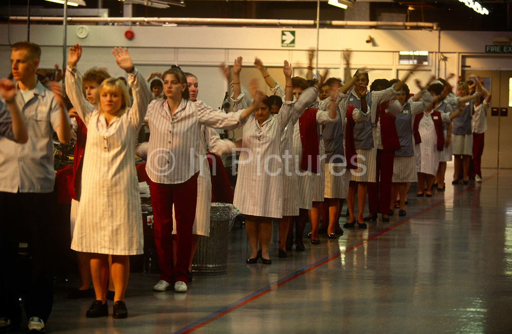 Workers with Alp Electric practice tai-chi before their shift starts at the company's Milton Keynes factory, England. Standing in lines on the factory floor, the British workers stretch their arms overhead to correctly start their working day, according to their Japanese owner's ethos. Alp Electric is one of the world's largest independent manufacturers of electromechanical components, headquartered in Tokyo, Japan. Established in 1948, Alp Electric produces electronic devices, including switchs, potentiometers, sensors, encoders and touchpads.