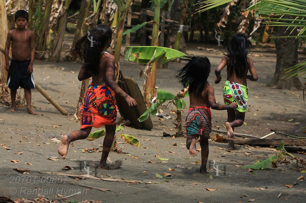 Girls of the indigenous Embera people run through their rustic traditional village at Playa de los Muertes on the Pacific coast; Darien National Park, Panama.
