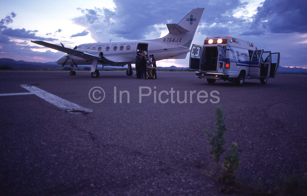 Loading a patient bound for hospital for treatment, on to a British Aerospace BAe-3101 Jetstream 31, an air ambulance on the runway at San Carlos Apache reservation in Arizona, USA. Native American Air Services, provides critical care level air ambulance services in Arizona. The company was founded in 1995 and is based in Mesa, Arizona. The San Carlos Reservation is one of the poorest Native American communities in the United States, with an annual median household income of approximately $14,000 in 2000, according to the US Census. About 60% of the people live under the poverty line, and 68% of the active labor force is unemployed
