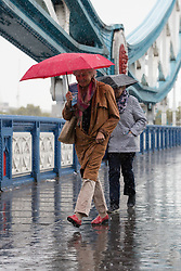 © Licensed to London News Pictures. 01/10/2016. LONDON, UK.  People cross Tower Bridge in London during heavy rain and wet weather this morning.  Photo credit: Vickie Flores/LNP