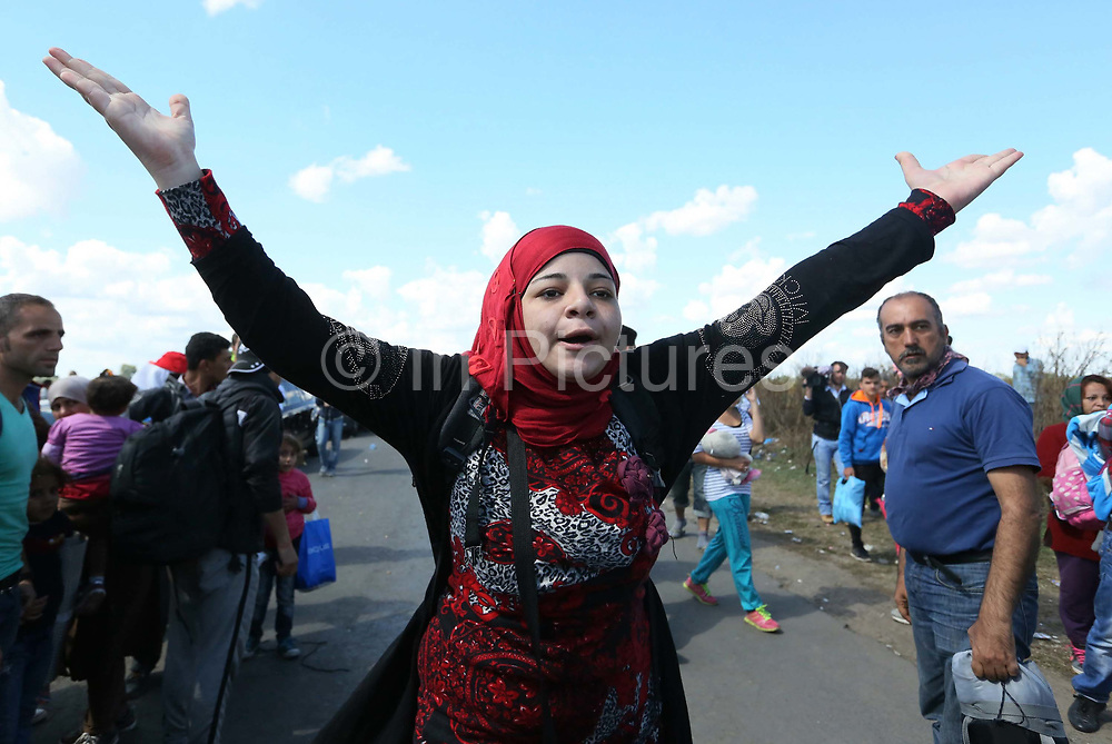 A woman gestures as Hungarian police contain migrants close to the Hungarian and Serbian border town of Roszke, Hungary, September 7 2015. The UN's humanitarian agencies are on the verge of bankruptcy and unable to meet the basic needs of millions of people because of the size of the refugee crisis in the Middle East, Africa and Europe, senior figures within the UN have told the media.