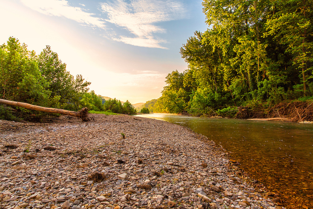 Sunrise Light Peeks Over The Trees Along The Buffalo River, America's first national river, begins its 132-mile tumble down toward the White River in the upper Ponca wilderness, some of the most remote and rugged country in the Ozarks. This stretch of the river is not suitable for floating, has little access and is mostly seen only be dedicated hikers. But the river reaches the historic Boxley Valley and begins a peaceful meandering that stretches the length of the long, narrow break in the hills before it begins its magnificent sweeps around the high limestone bluffs for which it is famous.