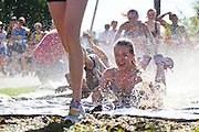 Teenage girls tumble through a Slip 'n Slide at the 2012 Bolder Boulder 10K road race in Boulder, Colorado.