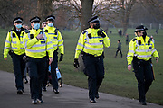 A day after London Mayor Sadiq Khan announced the spread of Covid is said to be out of control, Met police officers walk towards a group of Covid-deniers who are challenging lockdown rules and authoritarian control at passing south Londoners in Brockwell Park in Lambeth and during the third pandemic lockdown, on 9th January 2021, in London, England. The Coronavirus infection rate in London has exceeded 1,000 per 100,000 people, based on the latest figures from Public Health England although the Office for National Statistics recently estimated as many as one in 30 Londoners has coronavirus.