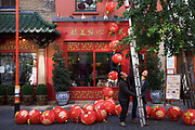 Two Chinese workmen work as a team attaching paper lanterns to an Oriental shop during preparations in London's Chinatown for the mid-Autumn (also Lantern or Moon) Festival where paper lanterns are to hang. The Mid-Autumn Festival, also known as the Moon Festival or Zhongqiu Festival is a popular harvest festival celebrated by Chinese, Korean, and Vietnamese people, dating back over 3,000 years to moon worship in China's Shang Dynasty. In Malaysia, Singapore, and the Philippines, it is also sometimes referred to as the Lantern Festival or Mooncake Festival. The Mid-Autumn Festival is held on the 15th day of the eighth month in the Chinese calendar, which is in September or early October in the Gregorian calendar. It is a date that parallels the autumnal equinox of the solar calendar, when the moon is at its fullest and roundest.