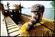 Soldier in coonskin cap frames colleague at tiller aboard replica of Lewis & Clark's keelboat in Lewis & Clark State Park; Onawa, Iowa