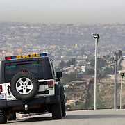 With Mexico as a backdrop, a U.S. Border Patrol agent patrols the border fence area that separates Tijuana, Mexico from San Diego, California for illegal entry. Please contact Todd Bigelow directly with your licensing requests.