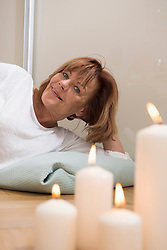Senior woman lying with pillow on the floor, burning candles in foreground, Munich, Bavaria, Germany