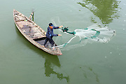 © Licensed to London News Pictures. 03/01/2012. A man cast a fishing net from a boat on the Thu Bon River in Hoi An, Vietnam. Photo credit : Stephen Simpson/LNP