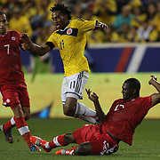 Juan Cuadrado, Colombia, is tackled by Doneil Henry, Canada, during the Colombia Vs Canada friendly international football match at Red Bull Arena, Harrison, New Jersey. USA. 14th October 2014. Photo Tim Clayton