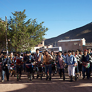 Villagers arrive and run through the streets of Macha during the Tinku Festival. Macha, Bolivia, 4th May 2010, Photo Tim Clayton .. up to 3000 thousands indigenous Bolivian indians descend on the isolated mountainous village of Macha 75 miles north of Potosi in the Bolivian Andes. The 600 year old pre-hispanic Bolivia Festival of Tinku sees villagers from all over the region march into town to be pitted against each other in a toe to toe fist to fist combat.. They dance and sing in traditional costume and drink 96% proof alcohol along with chicha, a fermented beverage made from corn. Townspeople and sometimes the police oversee proceedings who often use tear gas to try and control the villages, whipped into a fighting frenzy by the dancing and alcohol, but as the fiesta goes on things often escalate beyond their control, with pitched battles between rival villages break out,  The blood spilt is an offering to the earth goddess - Pachamama - to ensure a good harvest for the coming year. Over the years dozens have died, yet the rite continues.