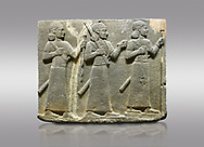 Picture & image of Hittite relief sculpted orthostat stone panel of Royal Buttress Basalt, Karkamıs, (Kargamıs), Carchemish (Karkemish), 900-700 B.C. Warriors. Anatolian Civilisations Museum, Ankara, Turkey.<br /> <br /> Three figures each with a long dress, a thick belt and curly hair. The figure in front holds a spear with a broken tip in his left hand and a leafy branch in his right hand. The figure in the middle made his left hand a fist, and he carries a tool with his right hand at the level of his head. They are followed with a figure holding a sceptre in his left hand. All three have each a long sword at their waist. <br /> <br /> Against a gray background. .<br />  <br /> If you prefer to buy from our ALAMY STOCK LIBRARY page at https://www.alamy.com/portfolio/paul-williams-funkystock/hittite-art-antiquities.html  - Type  Karkamıs in LOWER SEARCH WITHIN GALLERY box. Refine search by adding background colour, place, museum etc.<br /> <br /> Visit our HITTITE PHOTO COLLECTIONS for more photos to download or buy as wall art prints https://funkystock.photoshelter.com/gallery-collection/The-Hittites-Art-Artefacts-Antiquities-Historic-Sites-Pictures-Images-of/C0000NUBSMhSc3Oo