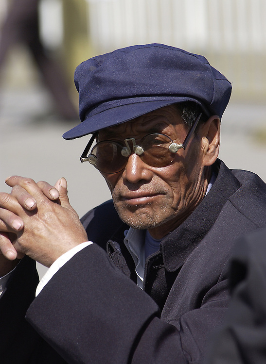 Man at Tiananmen Square in Beijing, China wearing Mao-era issued clothes.
