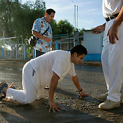 Tony Medina crawls at the feet of Alberto Salinas during a penance to the tomb of Nino Fidencio in Espinazo, Nuevo Leon while his brother Joe Medina stands by his side just after sunrise. Medina, who one day wishes to become a medium like Salinas, crawled over half a mile from the pepper tree to Fidencio's tomb as a sign of devotion to the Mexican folk saint. <br /> Nathan Lambrecht/The Monitor