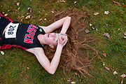 Aspen High School's Edie Sherlock lays on the ground catching her breath after she competed in the 2019 Colorado 3A Region 1 Cross Country meet at Crown Mountain Park in El Jebel, Colorado.