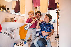 Father and his sons brushing their teeth in bathroom, Munich, Germany