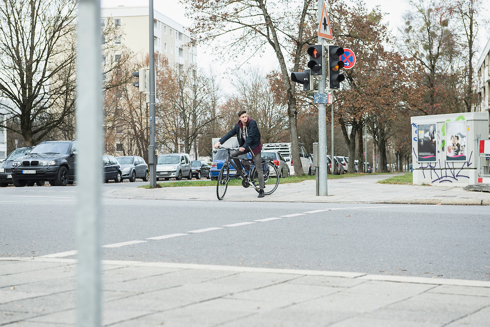 Young man with bicycle in the city waiting by the red traffic light, Munich, Bavaria, Germany