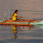 """Lady off to the shops in a small wooden Bunka.<br /> <br /> The SARANGANS showcase enormous cultural diversity of Blaan, Tboli, Tagakaolo, Kalagan, Manobo, Ubo, Muslim tribes and Christian settlers. Hospitable and fun-loving """"Sarangans"""" (people of Sarangani) adhere to a unified direction for development.<br /> Muslim consists of 7 groups; the Lumads, 17; and the migrant settlers, at least 20. The Blaans characterize the largest minority and are distributed in the municipalities of Malapatan, Glan, Alabel, Maasim, and Malungon. A bulk of this tribe is found in Malapatan constituting 37% of the municipal household population.<br /> The Maguindanaos are settled in the municipalities of Malapatan, Maitum, and Maasim; Tbolis reside mostly in Maitum, Kiamba, and Maasim while Tagakaolos subsist entirely in Malungon.<br /> Cebuano settlers are found in Glan and Alabel; Ilonggos are situated in Malungon while the Ilocanos live mostly in Kiamba and Maitum.<br /> Thus, Sarangani's mixed population of Cebuano-speaking Blaans and Muslims in the east coast, Ilocano-speaking Tbolis, Manobos and Muslims in the west coast, and Ilonggo-speaking Blaans and Kaolos in the north uplands, is unique and in harmony."""