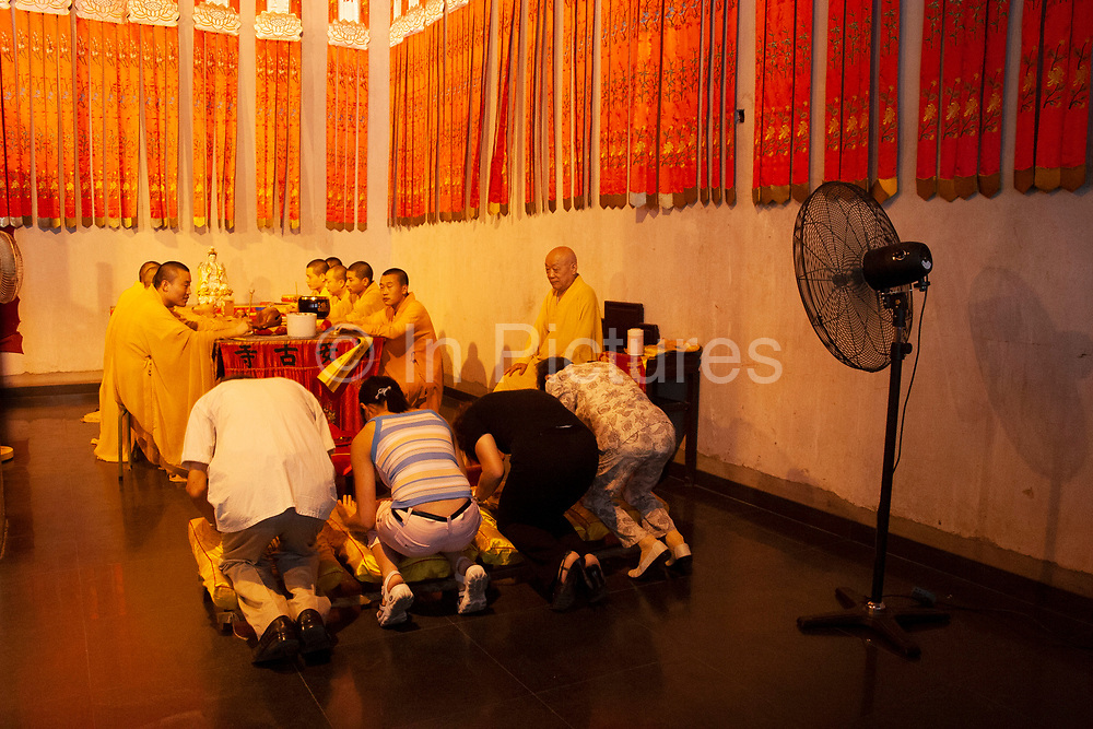 People praying in Jingan Temple in Shanghai, China. Jingan Temple, which means Temple of Peace and Tranquility, is a Buddhist temple on the West Nanjing Road in Shanghai, China. Jingan District, where it is located, is named after the temple. At this time the temple was being renovated and had concrete walls exposed.