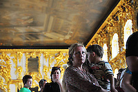 Summer visitors to the Hall of Light at the Catherine Palace at Tsarskoe Selo (Pushkin) near St. Petersburg, Russia listen to some of the building's history.